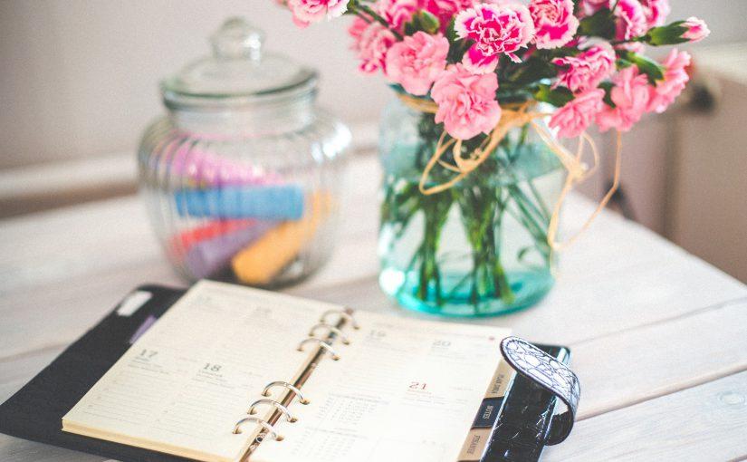 写真:机の上に手帳が広げられていて、ピンクの花が飾ってある