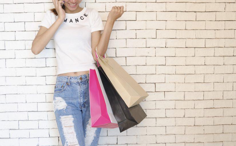 写真:ショッピングバックを持った女性が電話をしている